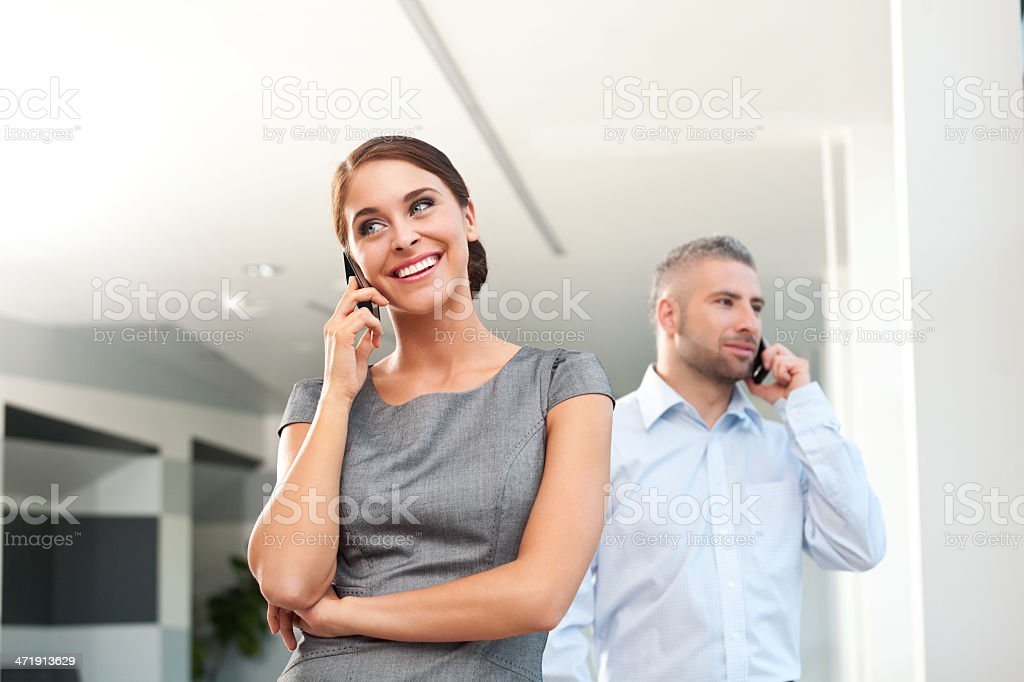 Business people on the phones Cheeful businesswoman and businessman talking on the phone. Adult Stock Photo
