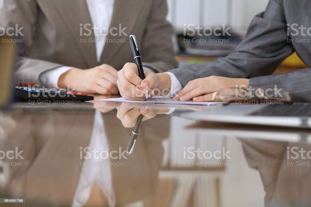 Business people or lawyers signing contract at meeting. Close-up of human hands at work - Royalty-free Adult Stock Photo