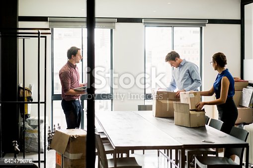 istock Business people packing boxes at table in office 642479676