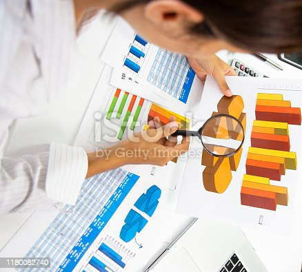business, people, paperwork, office and technology concept - businessman hands with calculator and pen writing and filing papers on table. Examining business graph and Finance management