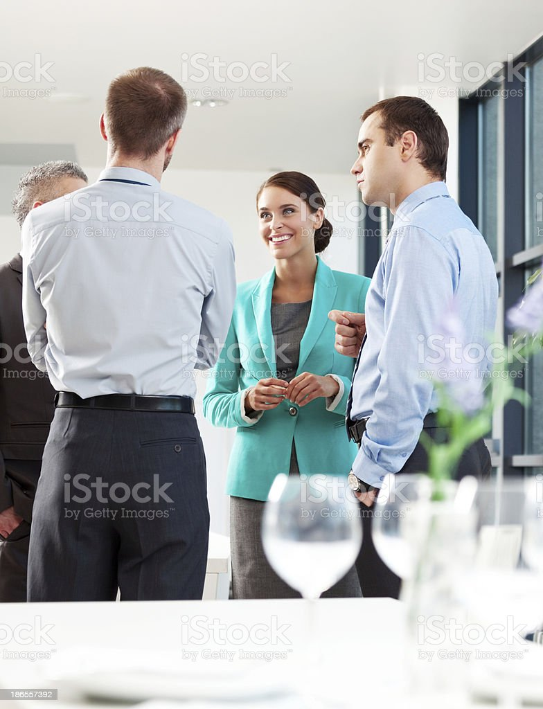 Business people Four business people waiting for a lunch, standing behind the table and discussing. Adult Stock Photo