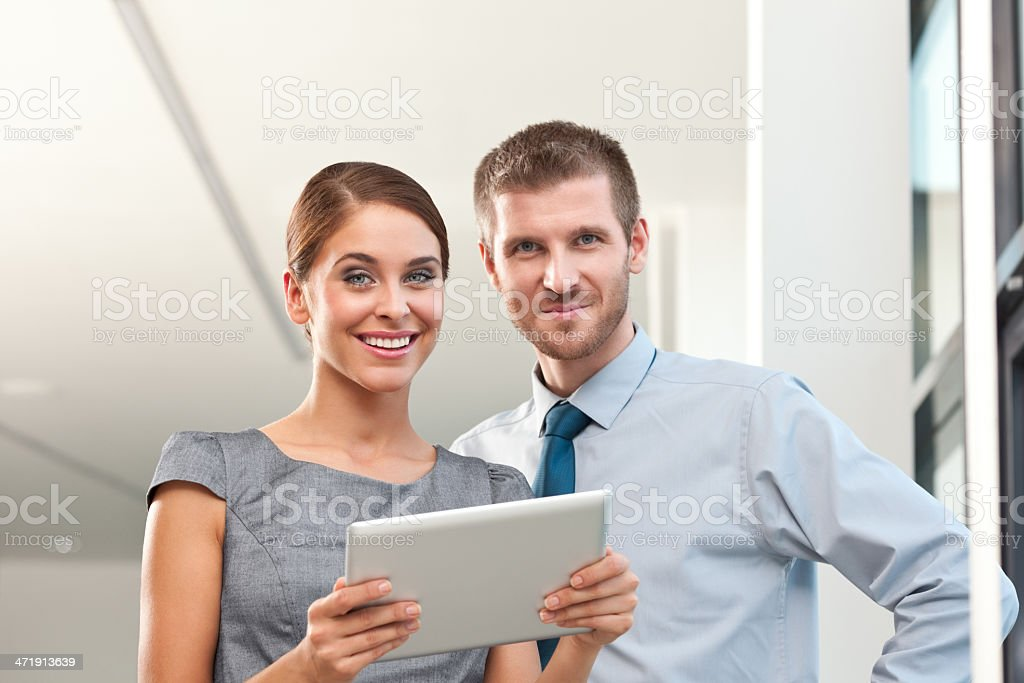 Business people Portrait of cheerful business couple smiling at the camera, businesswoman holding a digital tablet. Adult Stock Photo