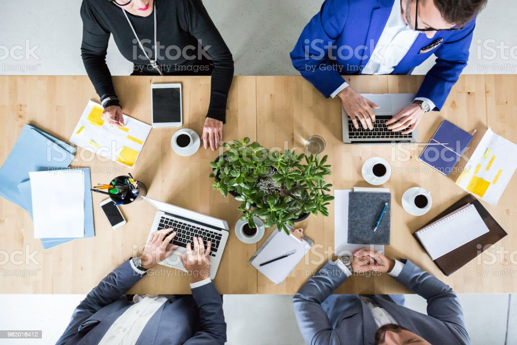 Business people planning new project Top view of four business professionals sitting around a table working on laptop and discussing new project. Active Seniors Stock Photo