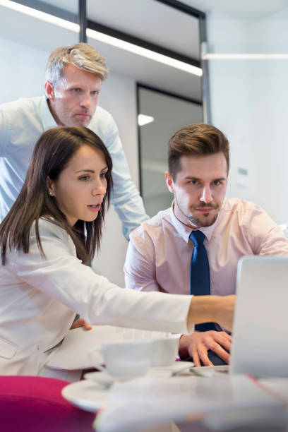 Business people planning over laptop at desk in office stock photo