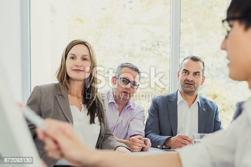 672116416istockphoto Business people planning their new ideas at flip chart 672093130