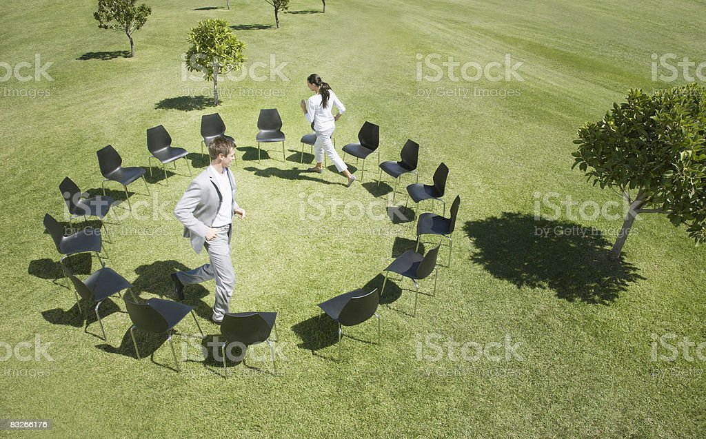 Business people playing musical chairs in field royalty-free stock photo