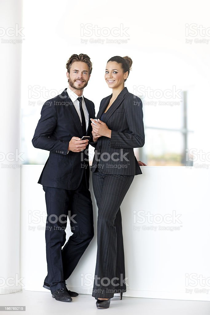 business people posing with phones in their hands stock photo