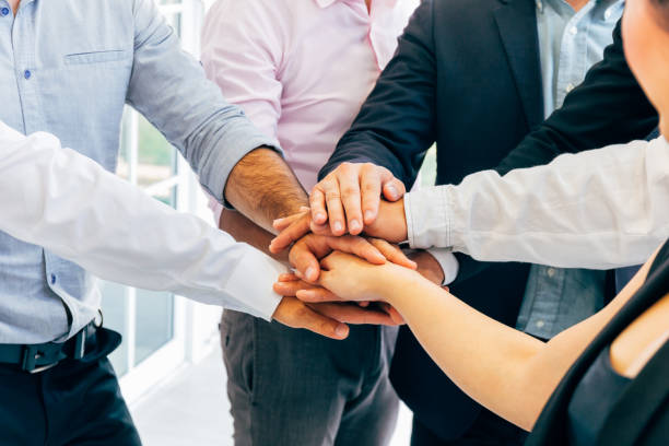 Business people putting hands togehter for unity stock photo