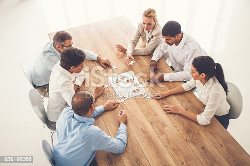 639198068 istock photo Business people putting puzzle pieces together at office 639198058