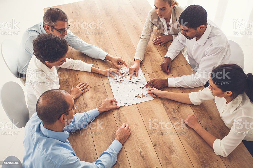 Business people putting puzzle pieces together at office stock photo