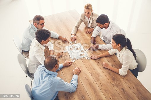 639198068 istock photo Business people putting puzzle pieces together at office 639198270