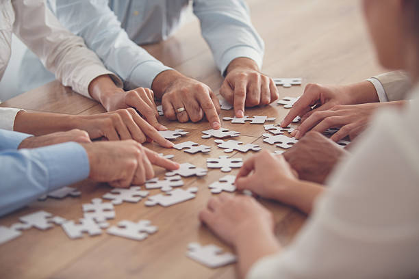 business people putting together jigsaw puzzle - jigsaw puzzle stock photos and pictures