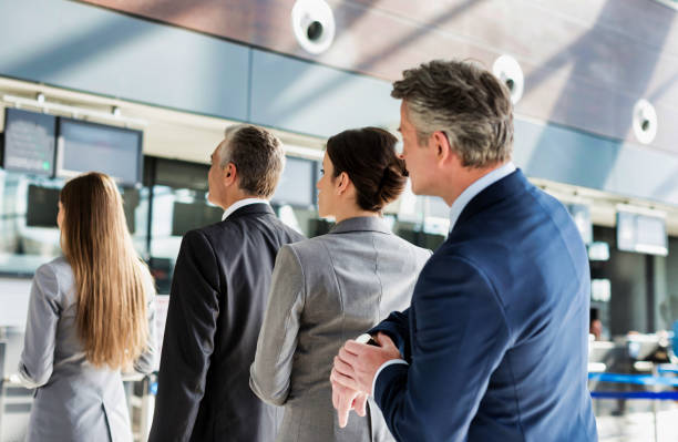Business people queueing for check in at airport stock photo
