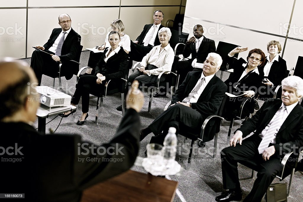 Business people raising hands on seminar royalty-free stock photo