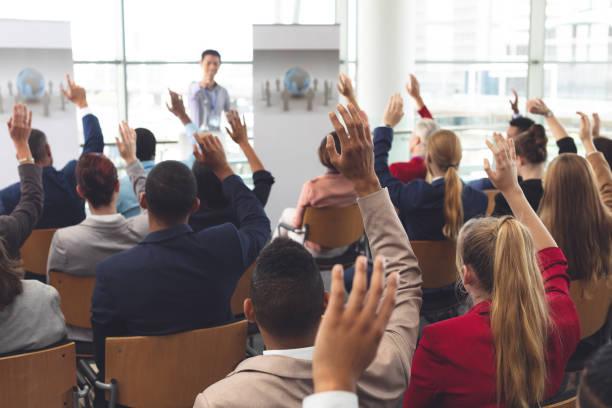 Geschäftsleute heben bei einem Business-Seminar die Hände – Foto