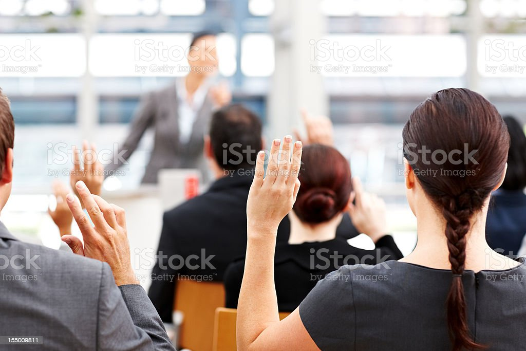Business People Raising Their Hands at a Conference royalty-free stock photo
