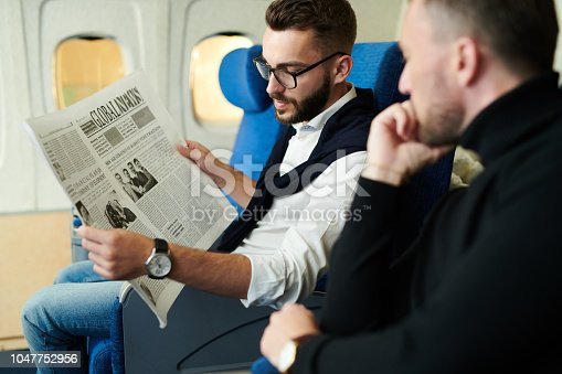 istock Business People Reading Newspaper in Plane 1047752956