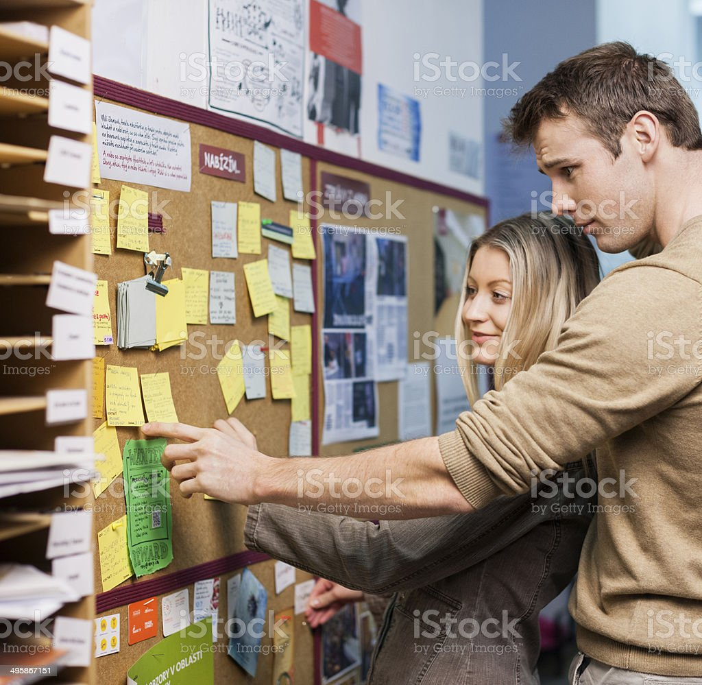 Business people reading reminders on bulletin board in office stock photo