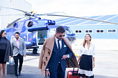 Latin ethnic business people of different ages are ready to travel by helicopter