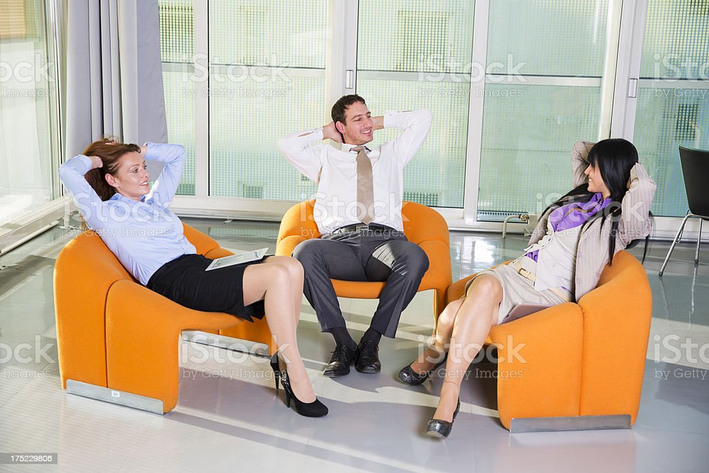 Business people relaxingin comfortable armchairs,chatting and smiling royalty-free stock photo
