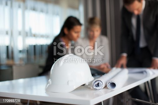 istock Business people reviewing blueprints in conference room 170993725