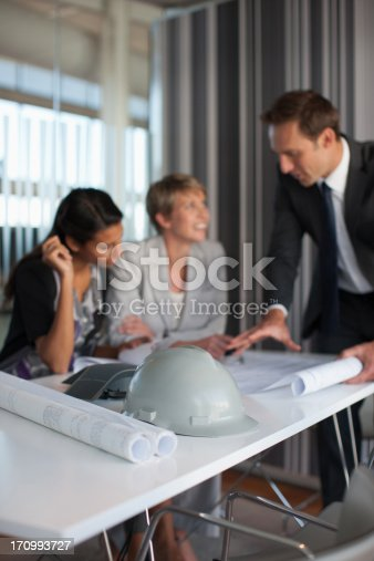 istock Business people reviewing blueprints in conference room 170993727