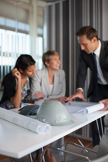 Business people reviewing blueprints in conference room stock photo