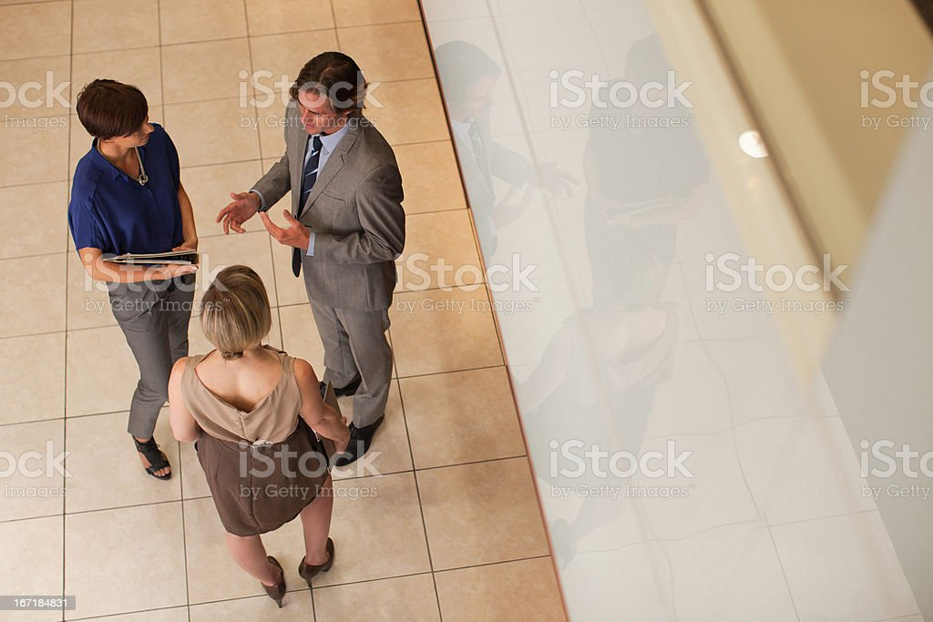 Business people reviewing paperwork in corridor royalty-free stock photo