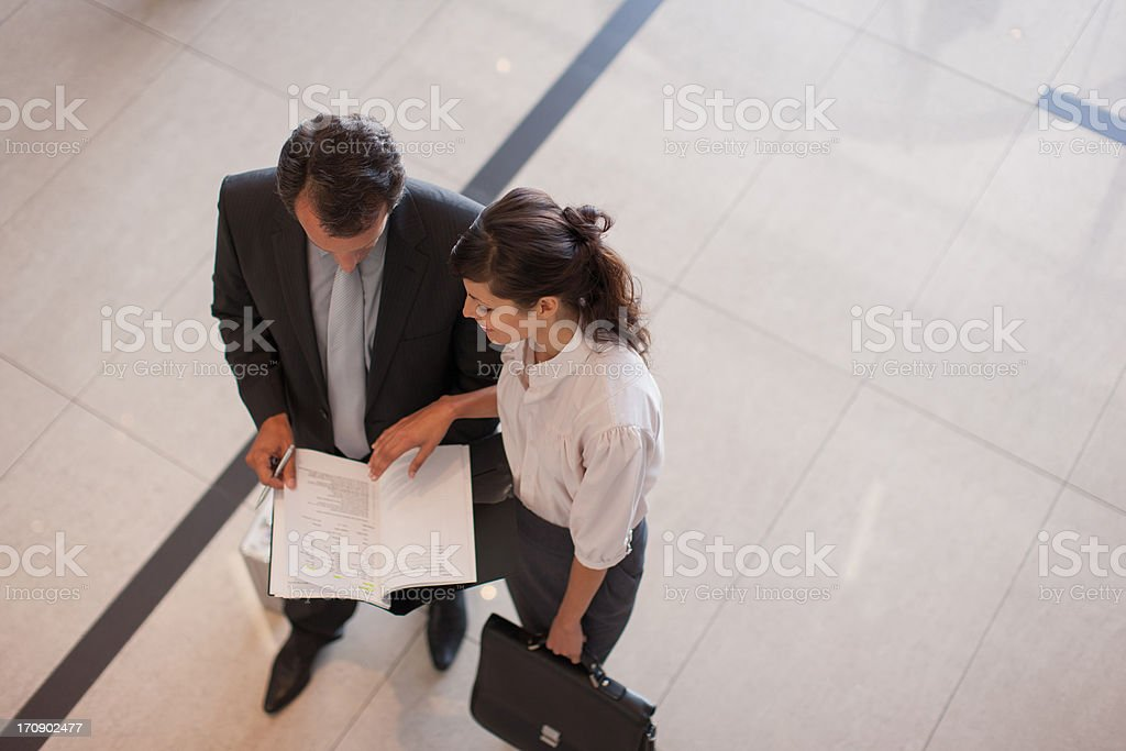 Business people reviewing report in lobby royalty-free stock photo