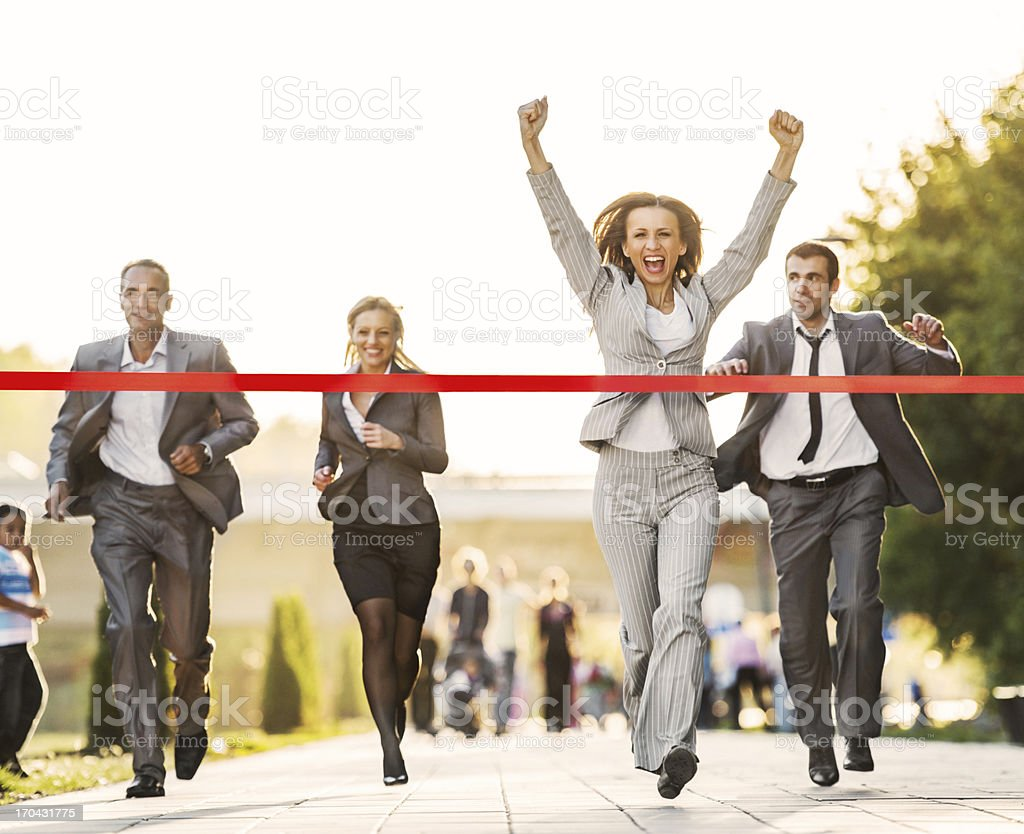 Business people running to finish, crossing red line. stock photo
