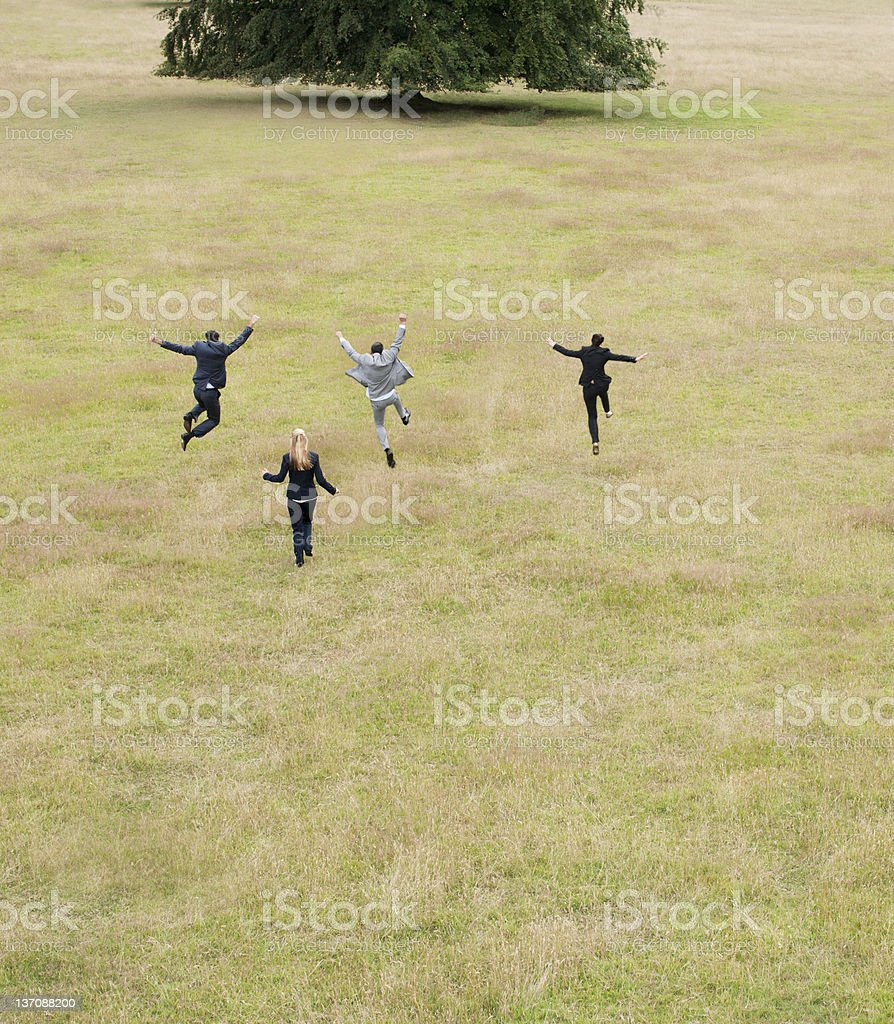 Business people running together in field stock photo