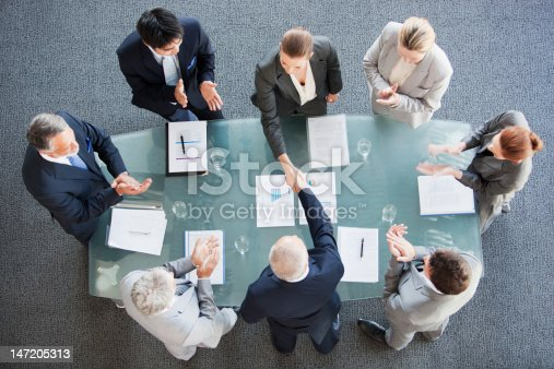 istock Business people shaking hands across conference room table 147205313
