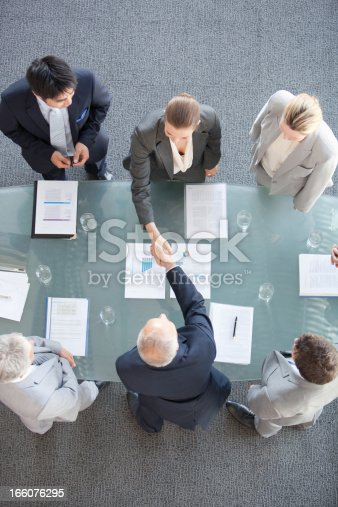 istock Business people shaking hands across conference room table 166076295