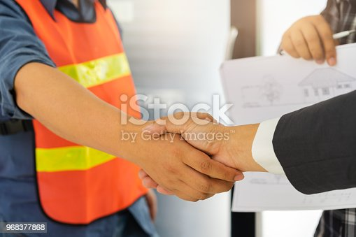 912867216istockphoto Business people shaking hands after successful building construction planning project and male architect standing holding a blueprint background. 968377868