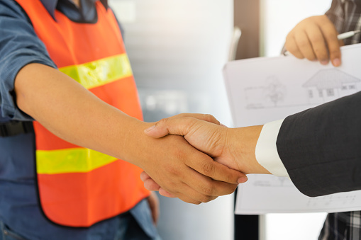 912867216 istock photo Business people shaking hands after successful building construction planning project and male architect standing holding a blueprint background. 968377868