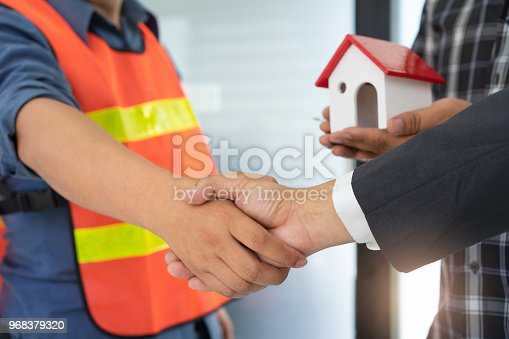 912867216istockphoto Business people shaking hands after successful building construction planning project. 968379320