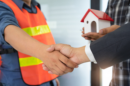 912867216 istock photo Business people shaking hands after successful building construction planning project. 968379320