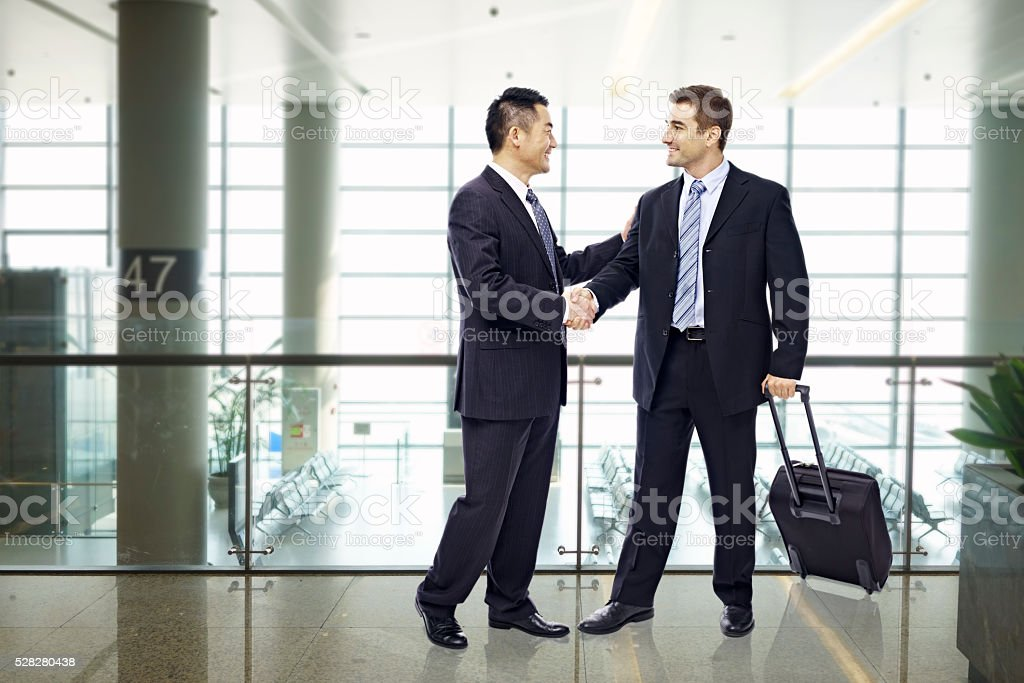 business people shaking hands at airport stock photo