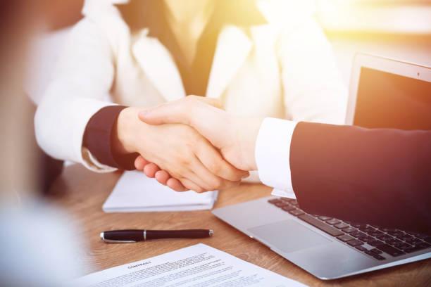 Geschäftsleute schütteln bei Treffen oder Verhandlungen im Büro die Hände. Handshake-Konzept. Partner sind zufrieden, weil sie einen Vertrag unterzeichnen. – Foto
