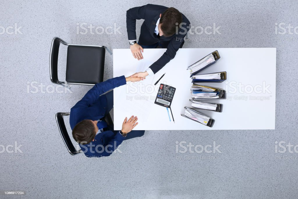 Business people shaking hands at meeting, view from above. Bookkeeper...
