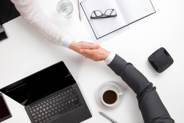 Business People Shaking Hands At Office Desk stock photo