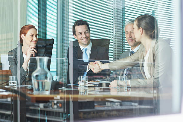 Business people shaking hands at table in conference room stock photo