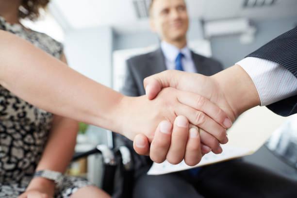Geschäftsleute schütteln Hände und beenden ein Meeting. Männliche und weibliche Hände in Handshake Nahaufnahme mit männlichen Kollegen im Hintergrund. – Foto