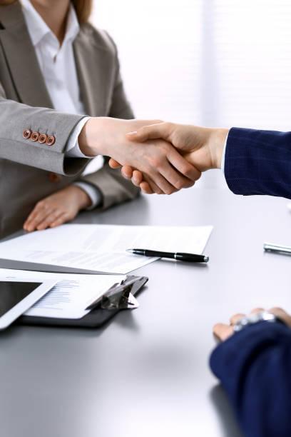 Geschäftsleute schütteln die Hände und beenden ein Treffen. Papers Signatur, Vereinbarung und Anwaltsberatung Konzept. – Foto