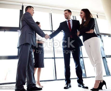 656005826istockphoto Business people shaking hands, finishing up a meeting 484427292