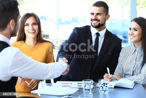 656005826istockphoto Business people shaking hands, finishing up a meeting 490287662
