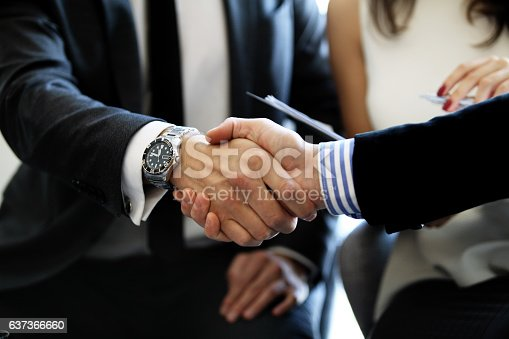 656005826istockphoto Business people shaking hands, finishing up a meeting. 637366660