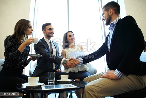 656005826istockphoto Business people shaking hands, finishing up a meeting. 637367016