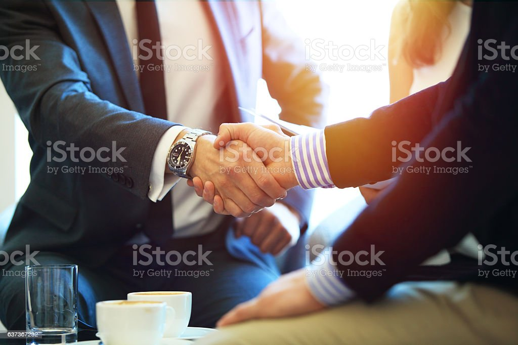 Business people shaking hands, finishing up a meeting. bildbanksfoto