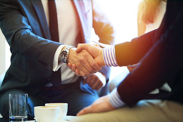 business people shaking hands, finishing up a meeting. - handshake stock pictures, royalty-free photos & images